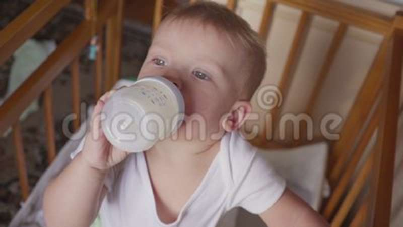 two year old boy drinking milk from plastic bottle in his bed