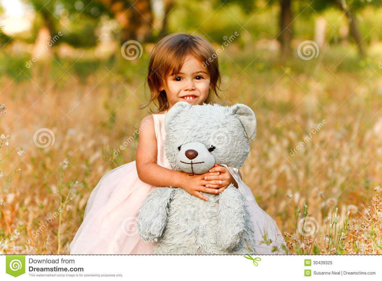 Two-year-old girl in field carrying stuffed animal