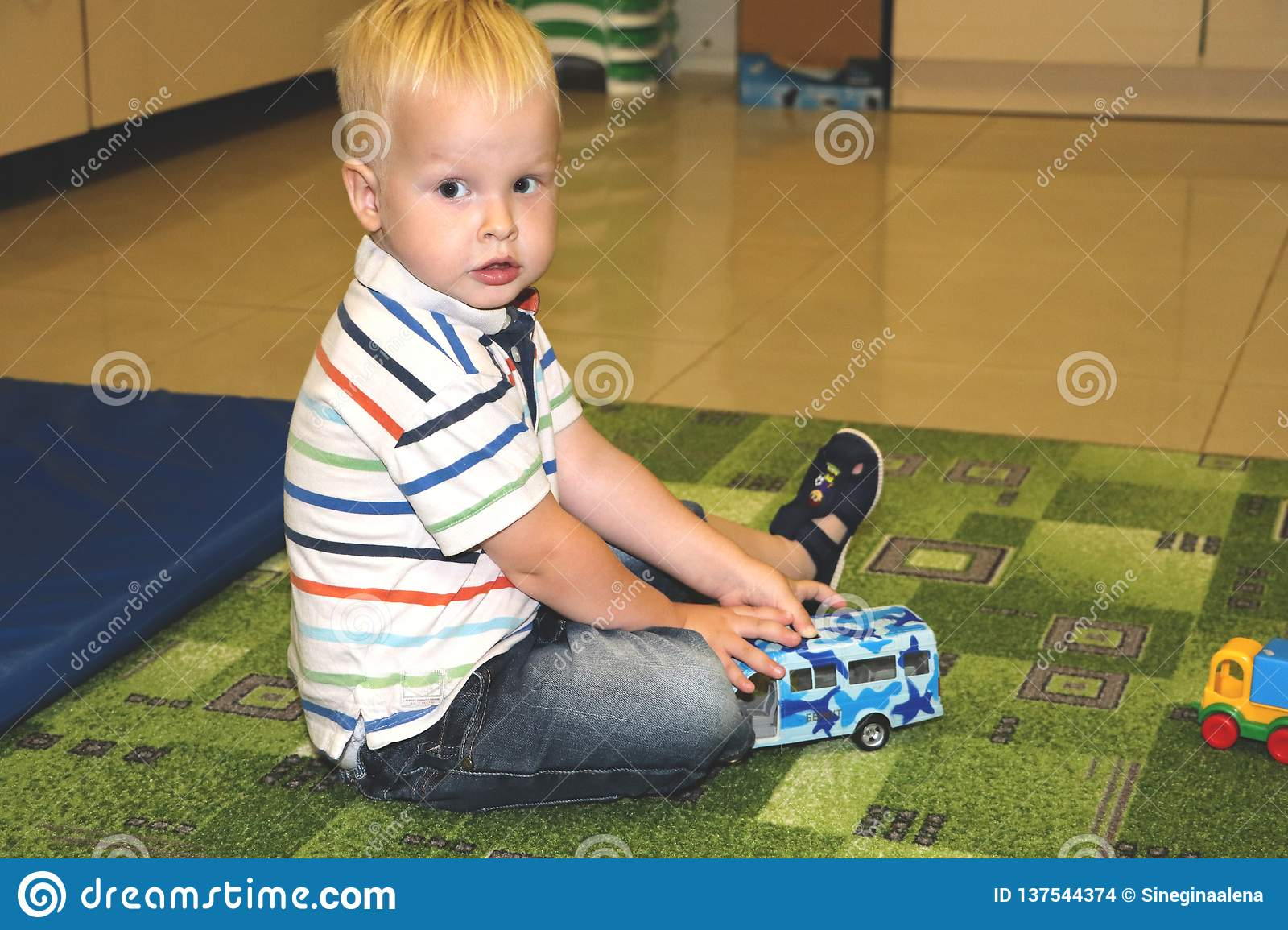 Two years child boy play with cars. Educational toys for preschool and kindergarten child, indoor playground, lifestyle concept