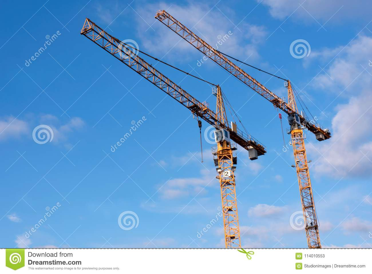 Two yellow construction cranes against blue sky with a few cloud