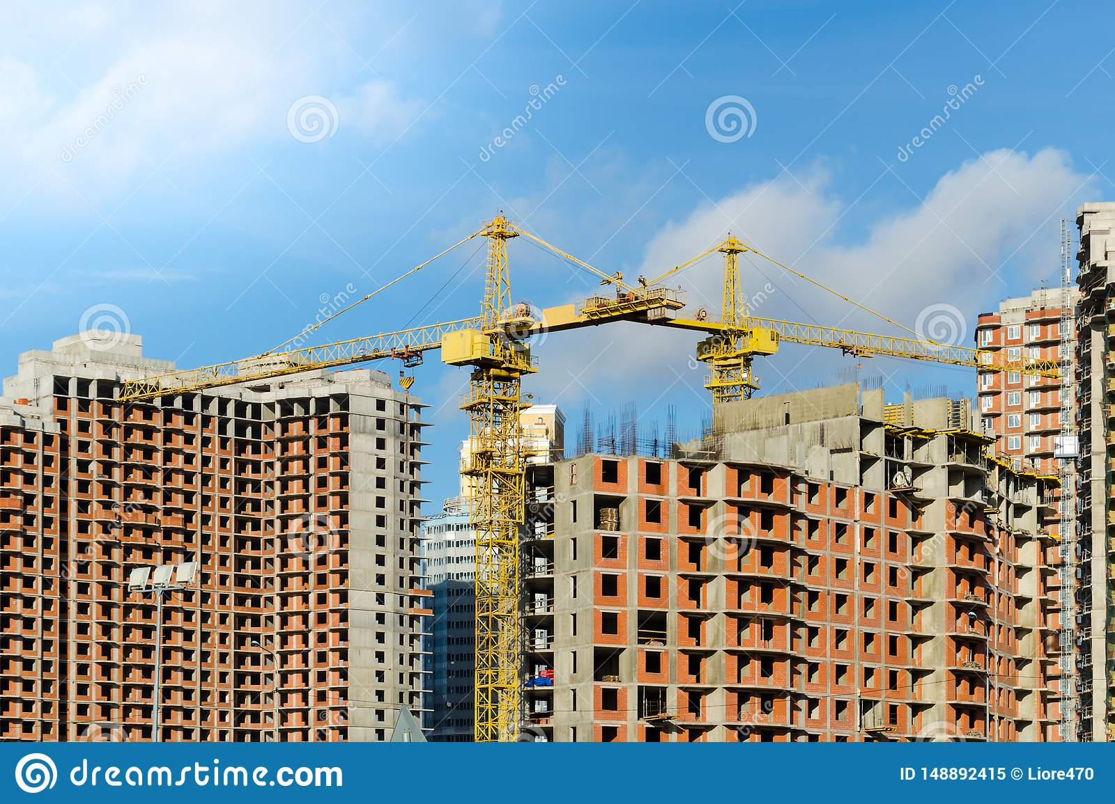 Two yellow construction cranes at the construction site of multi-storey brick houses against blue sky