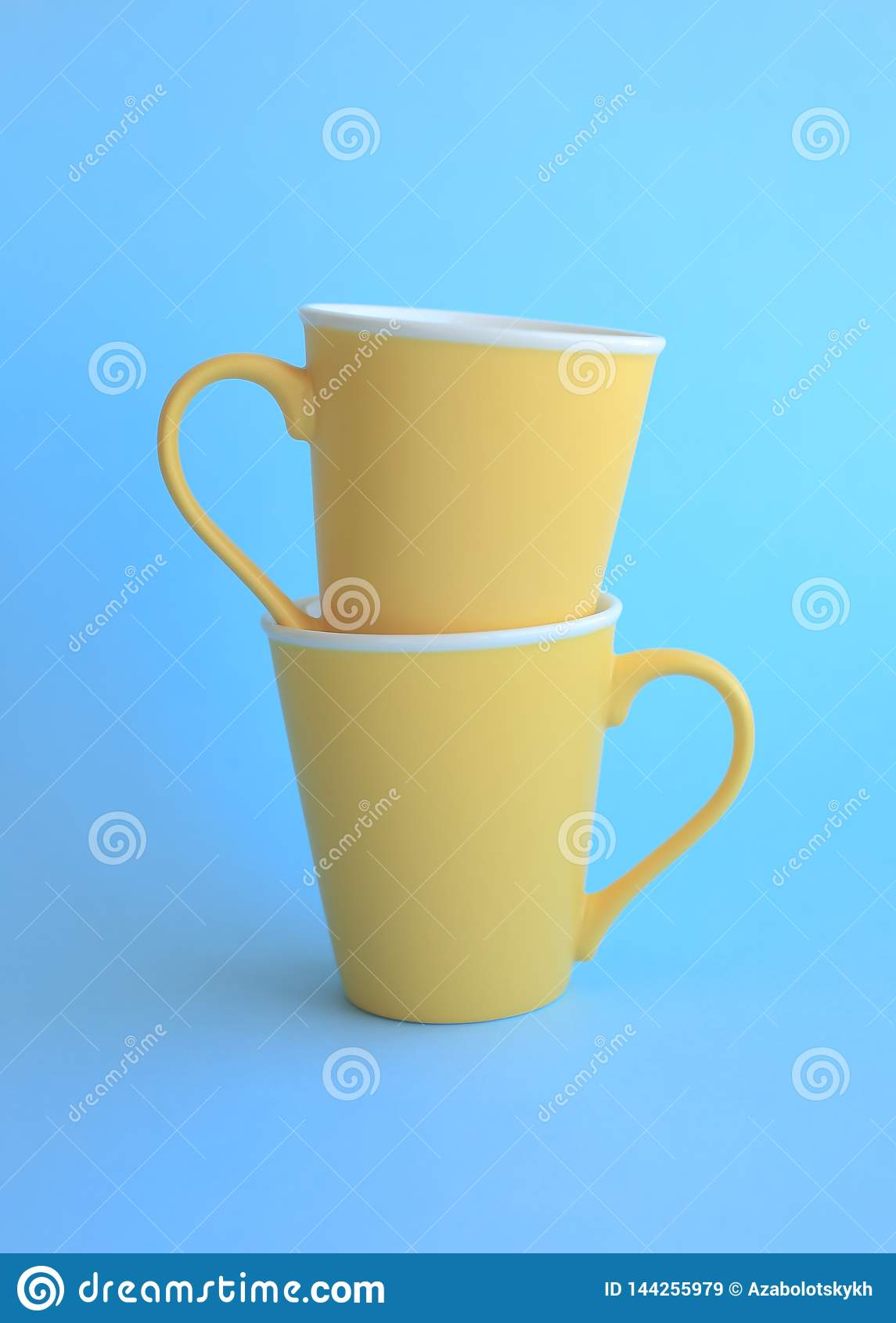 Two yellow cups on blue