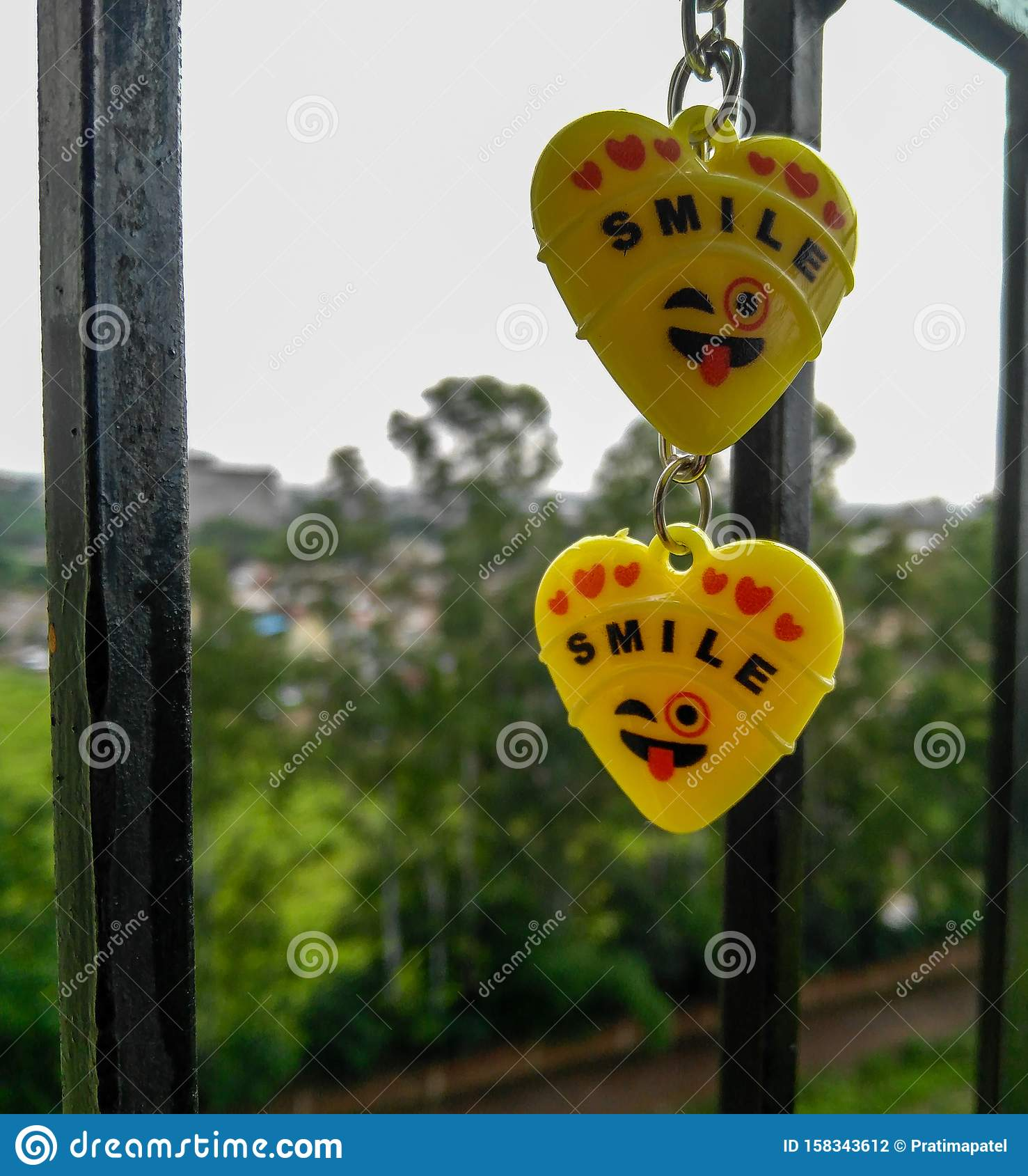 Two yellow hearts keychains, smile, balcony, natural background