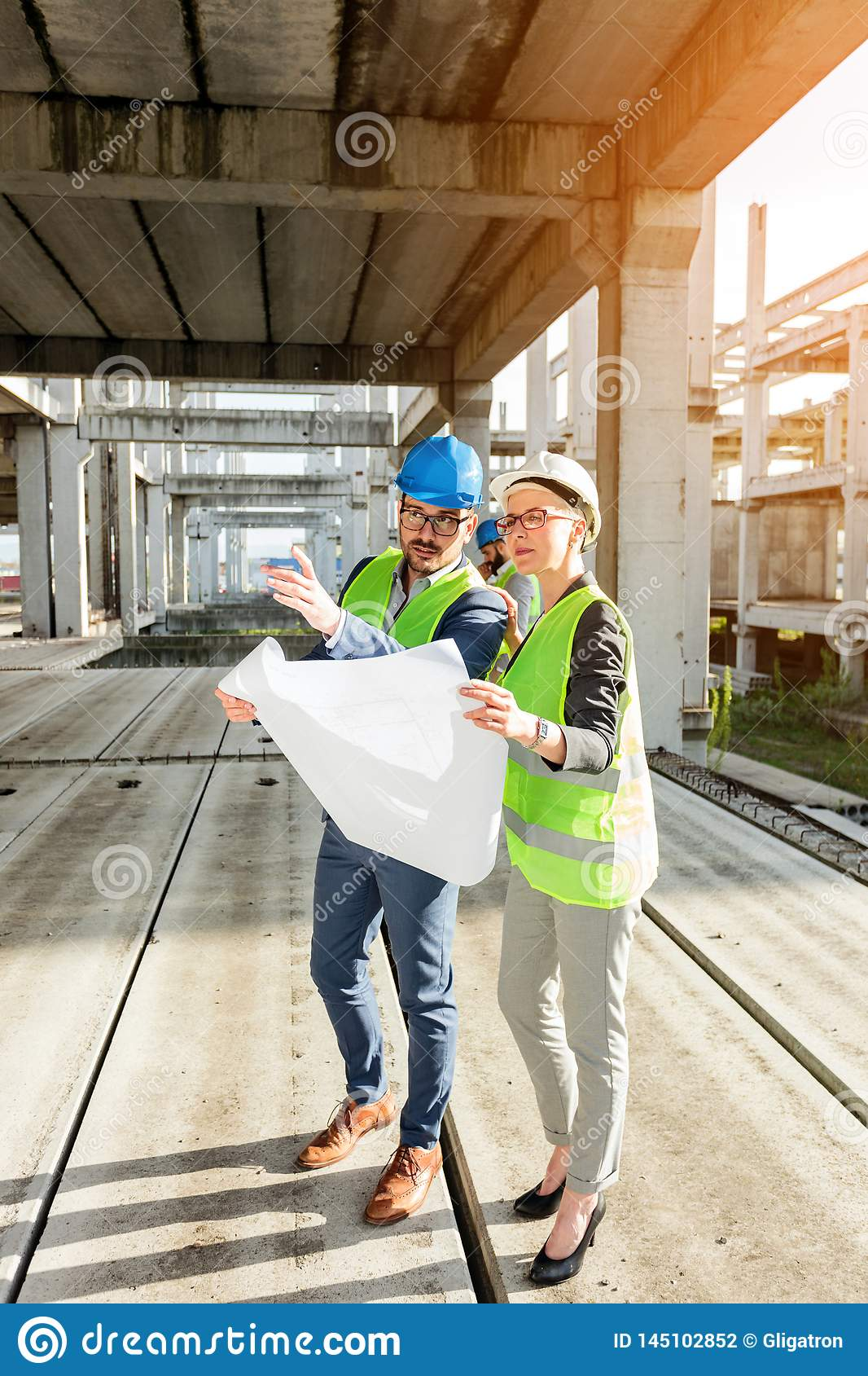 Two young architects visiting large construction site, looking at floor plans