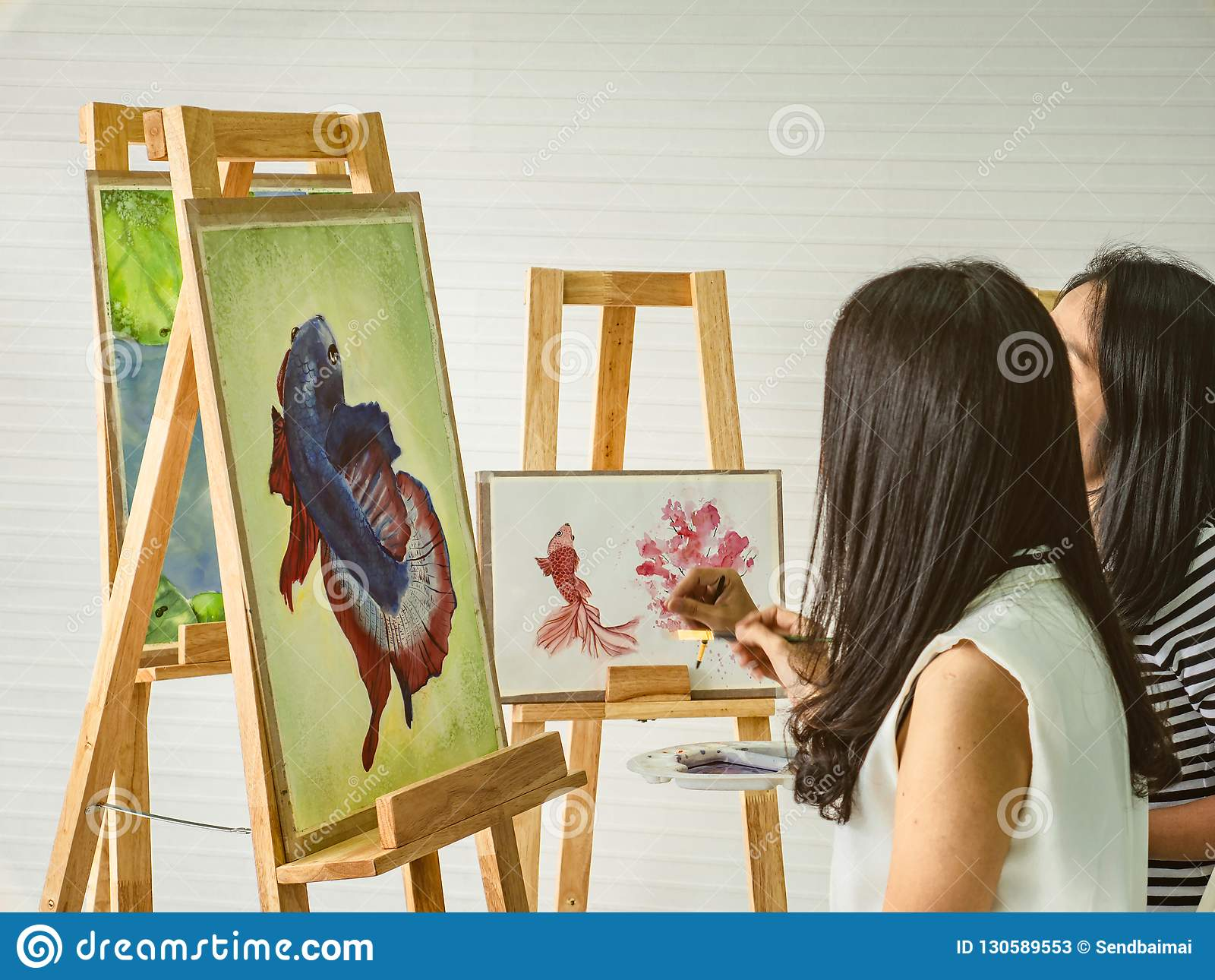 Two young asian woman artist dawning while useing ideas to think and create the best artwork