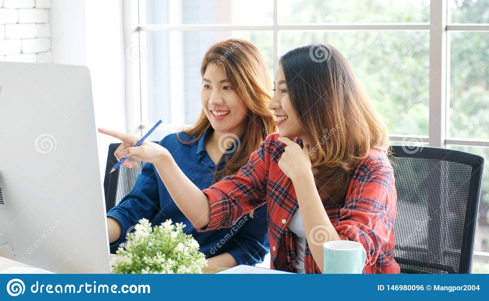 Two young asian women working with computer at home office with happy emotion, working at home, small business, office casual