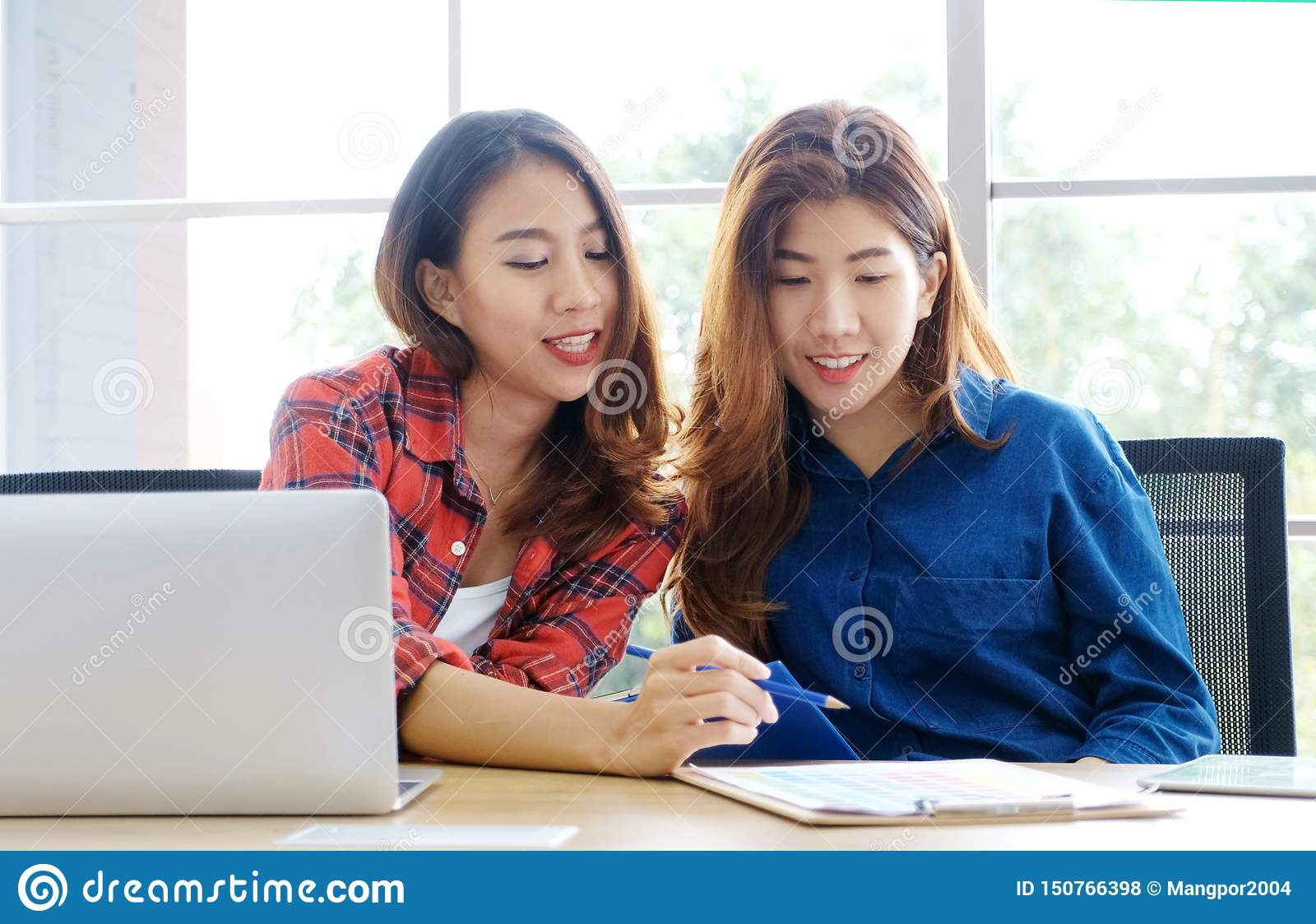 Two young asian women working with laptop computer at home office with happy emotion moment, working at home, small business,