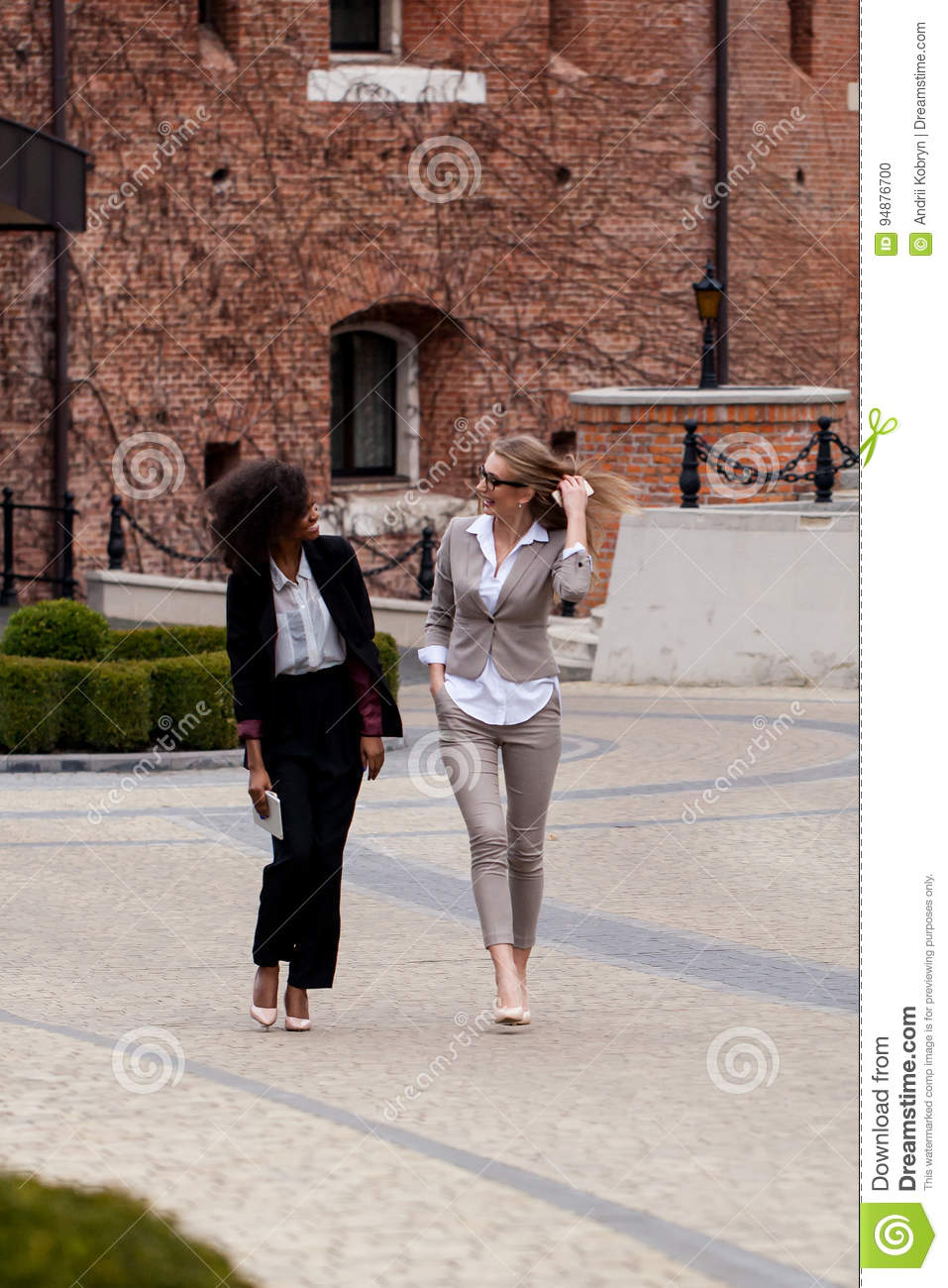 Two young and attractive businesswoman walking and having conversation. One woman is black with curly hair.