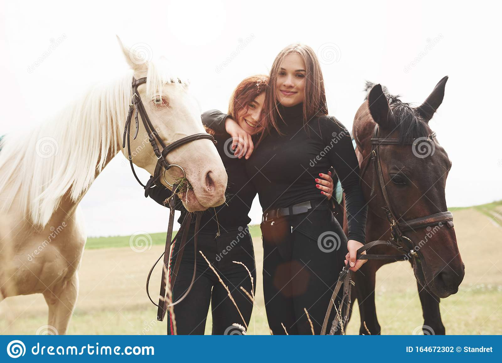 Two Young Beautiful Girls In Gear For Riding Near Their Horses They Love Animals Stock Photo Image Of Looking Friends 164672302