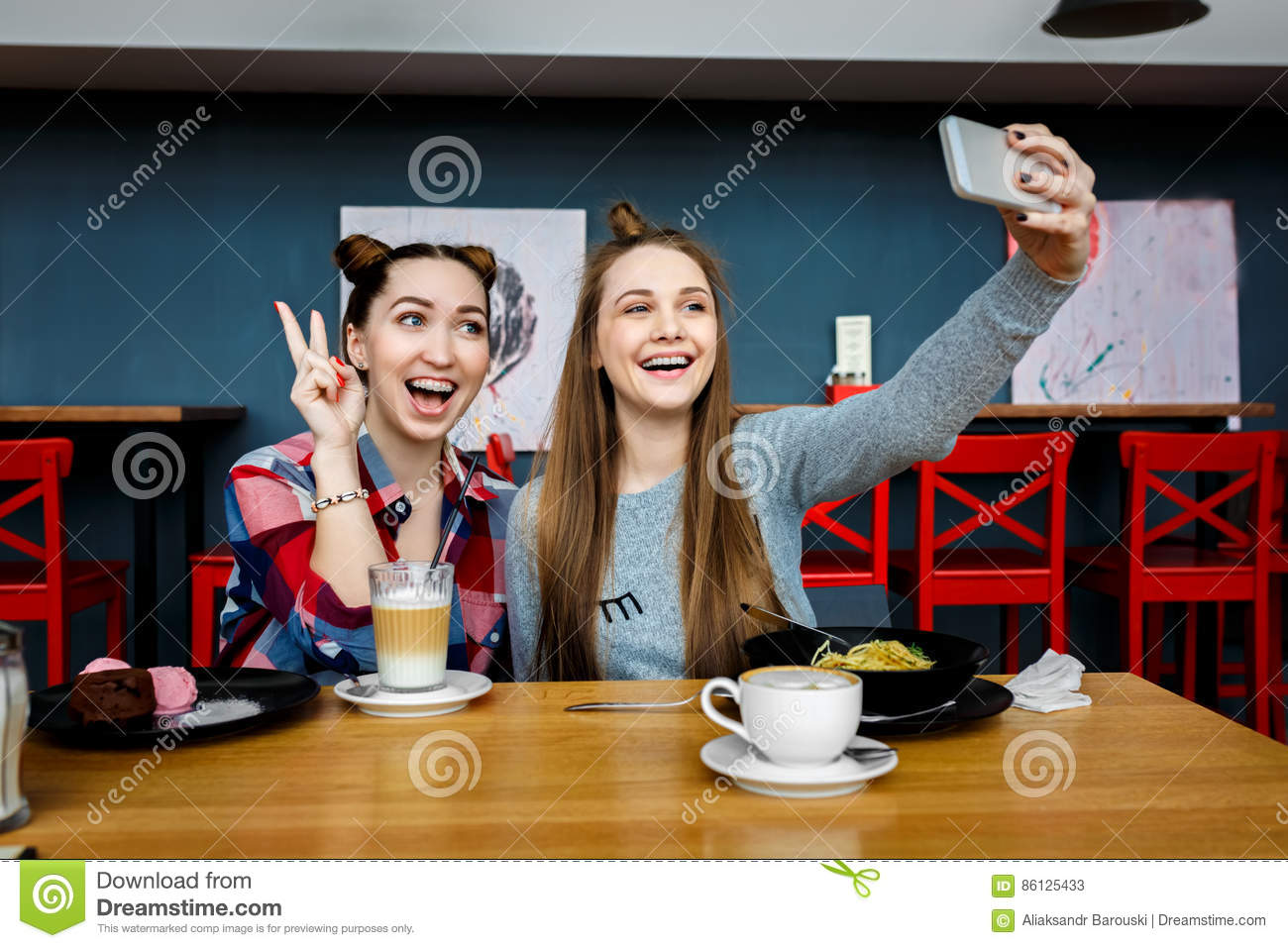Two young beautiful hipster women sitting at cafe, stylish trendy outfit, europe vacation, street style, happy, having