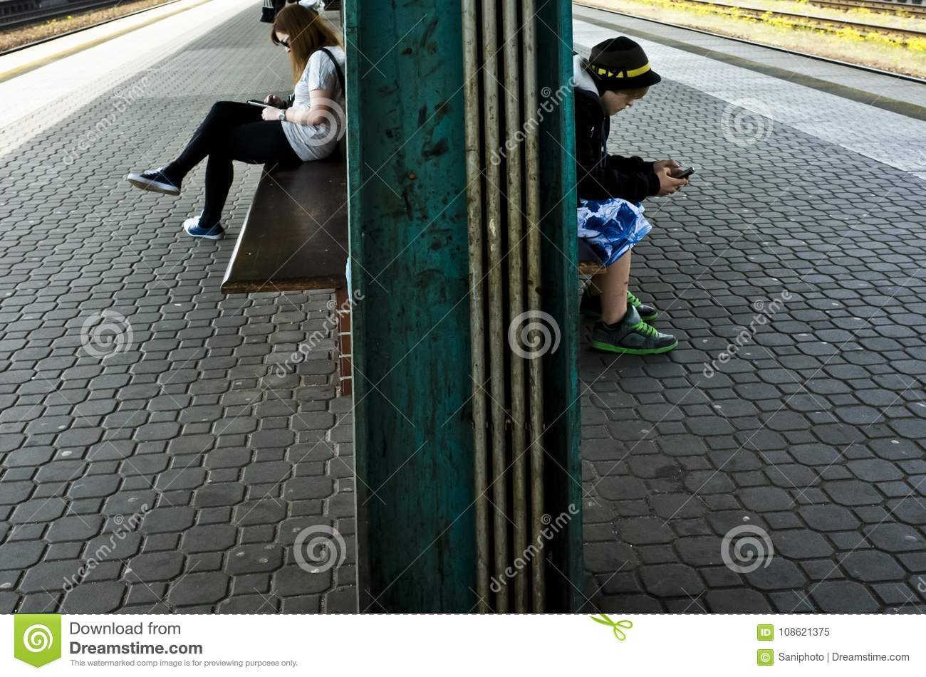 Young boy and girl sitting and waiting a train while using their cellphones