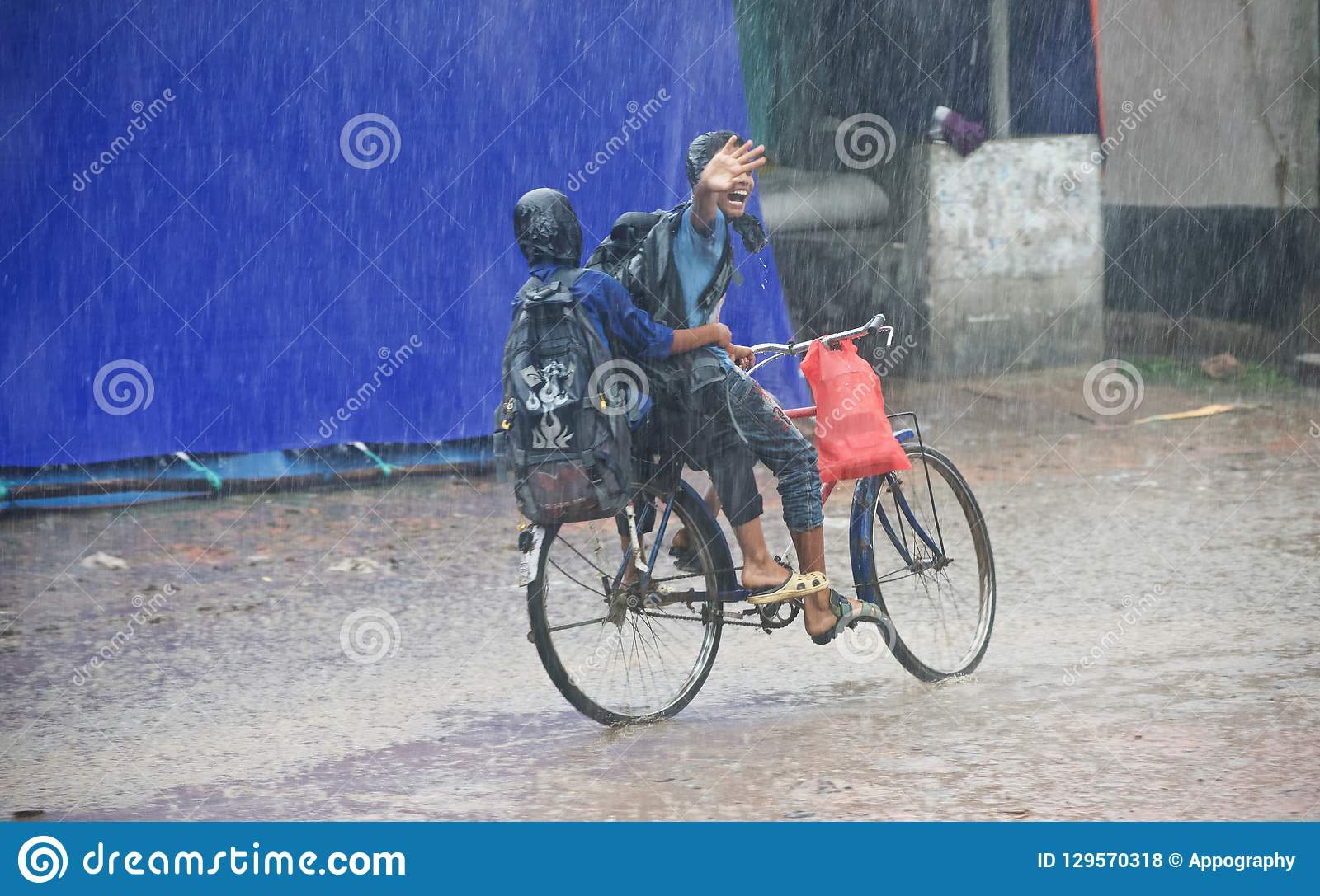 Two young boys riding a bicycle in the rain