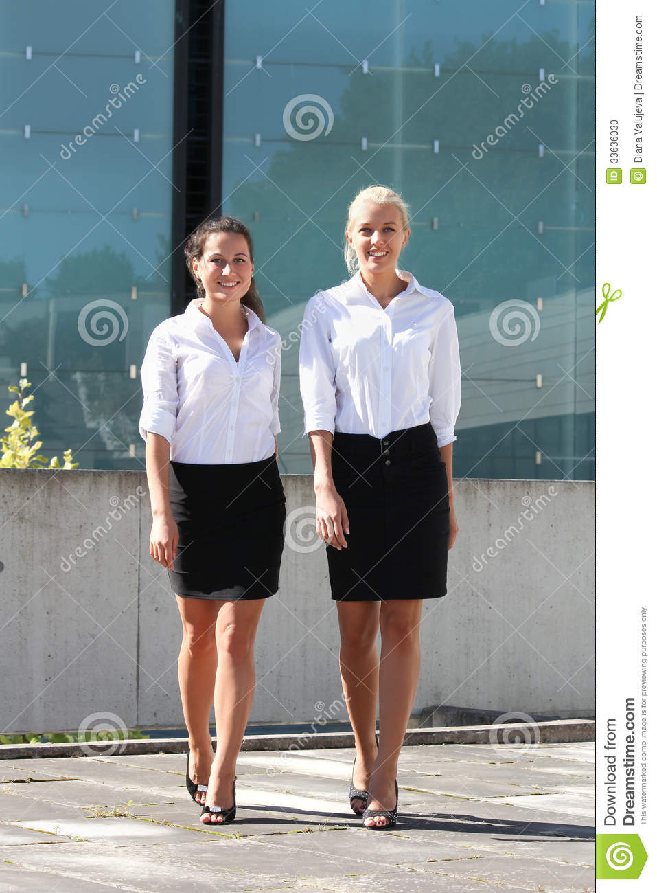 Two Young Business Women Walking In The Street Stock Photo
