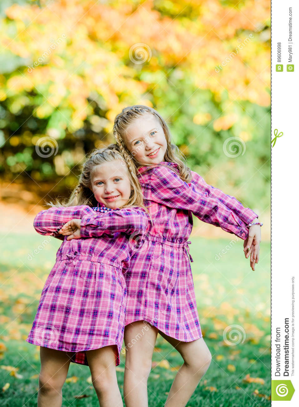 Two Young Caucasian Sisters Strike a Pose in Matching Pink Flannel Dresses