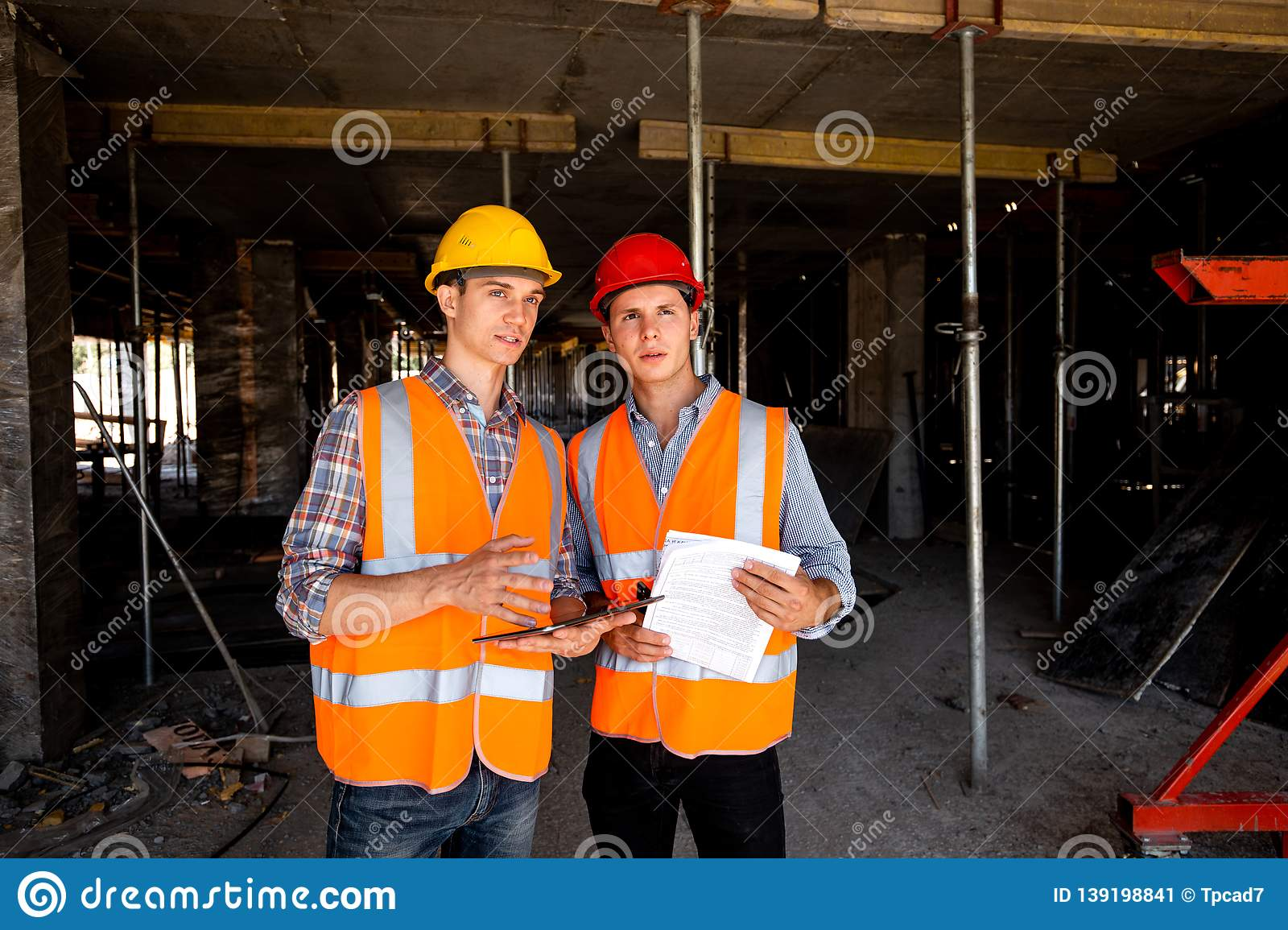 Two young civil engineers dressed in orange work vests and helmets work with tablet and documentation inside the