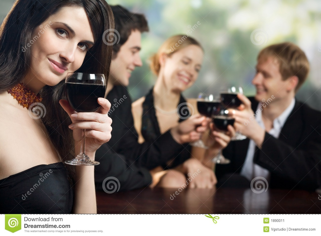 Two young couples with red wine glasses at celebration or party