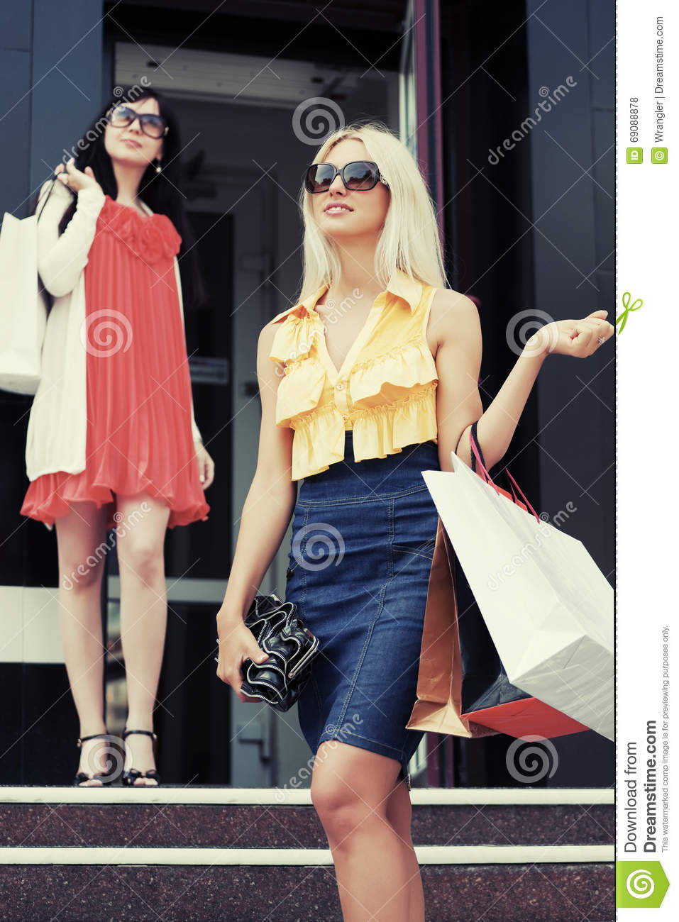 two young fashion women with shopping bags at the mall. Black Bedroom Furniture Sets. Home Design Ideas