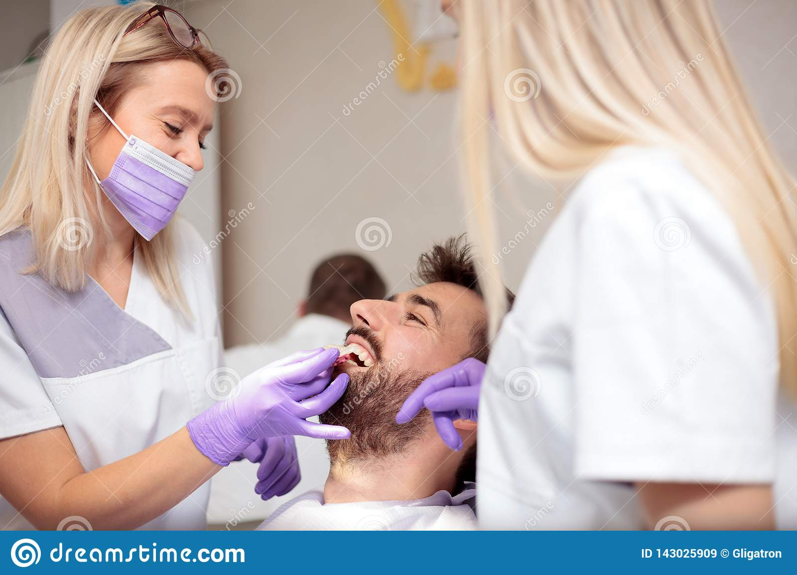 Two young female dentists working in dental clinic. Whitening male patient`s teeth and using tone chart to mach color