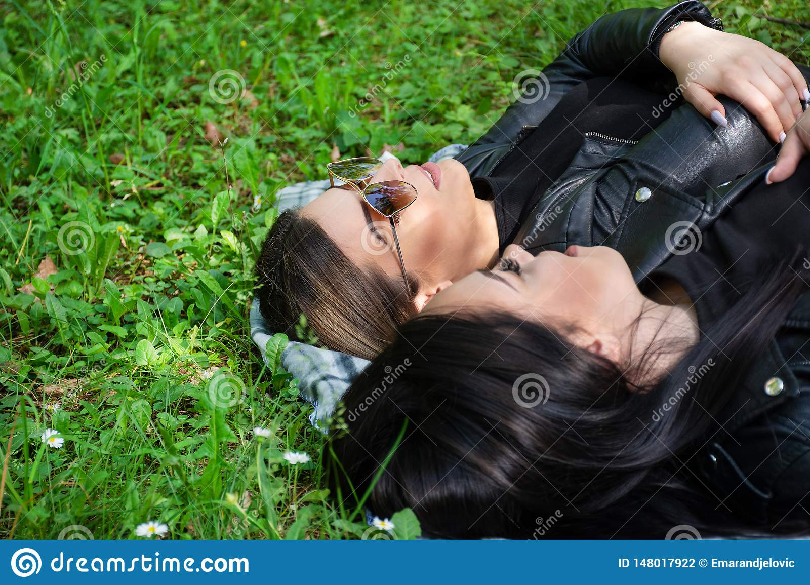 Two young girls lying down on the blanket and talking in a green meadow on a spring day in nature