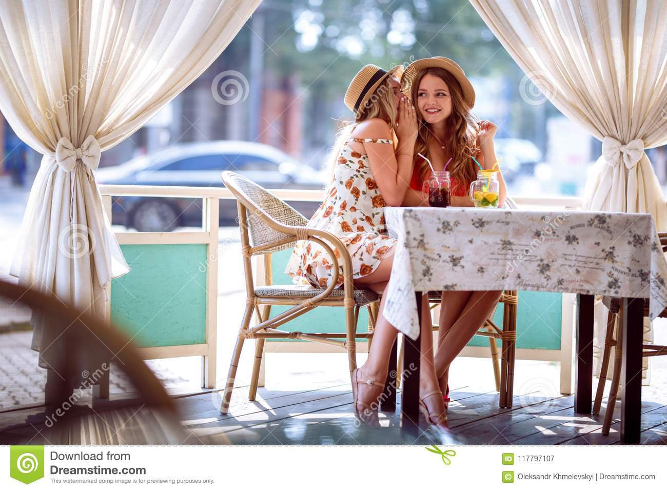 Two young girls share a secret in the ear sitting in a cafe