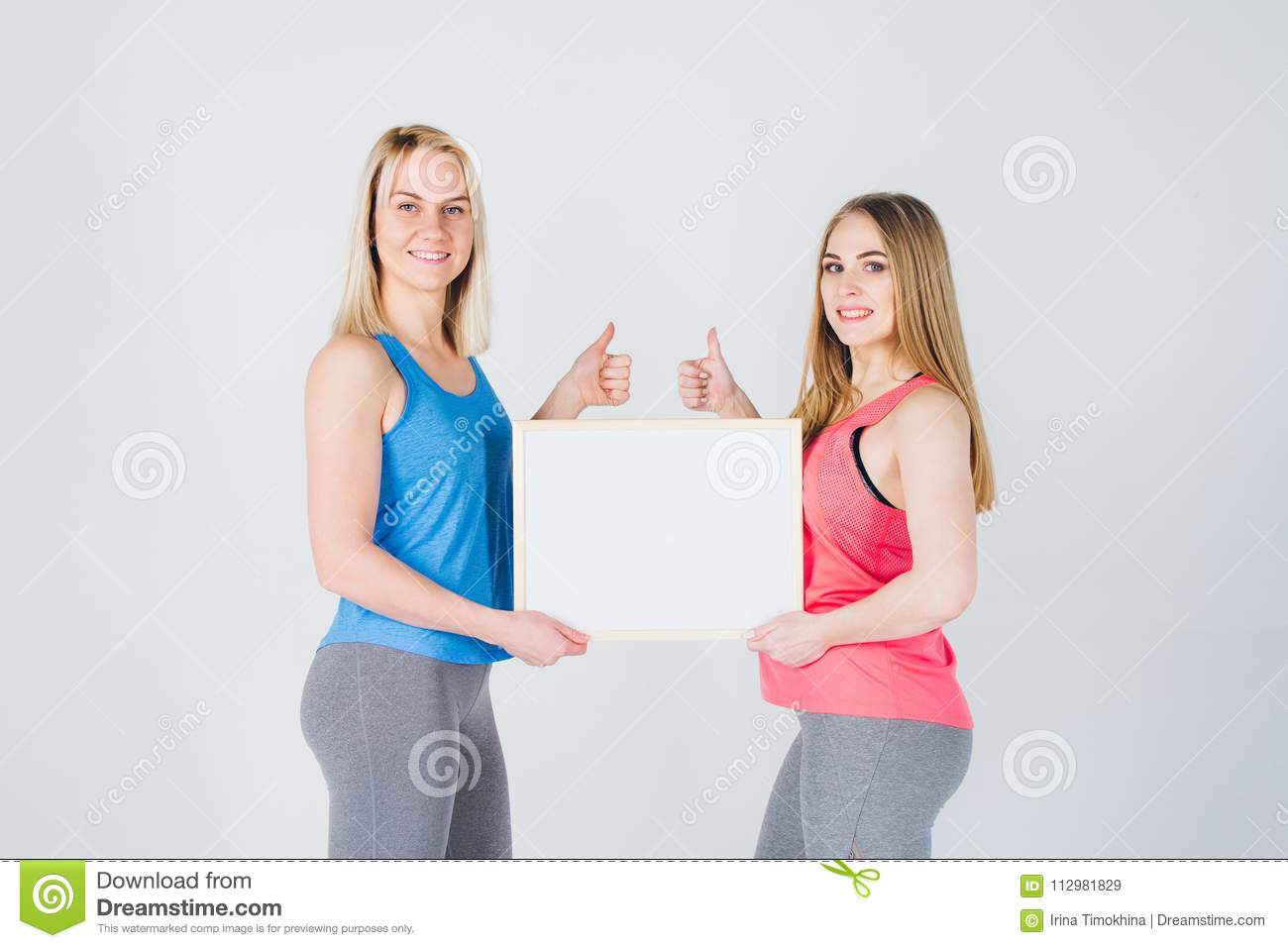 Two girls holding the frame with the ad