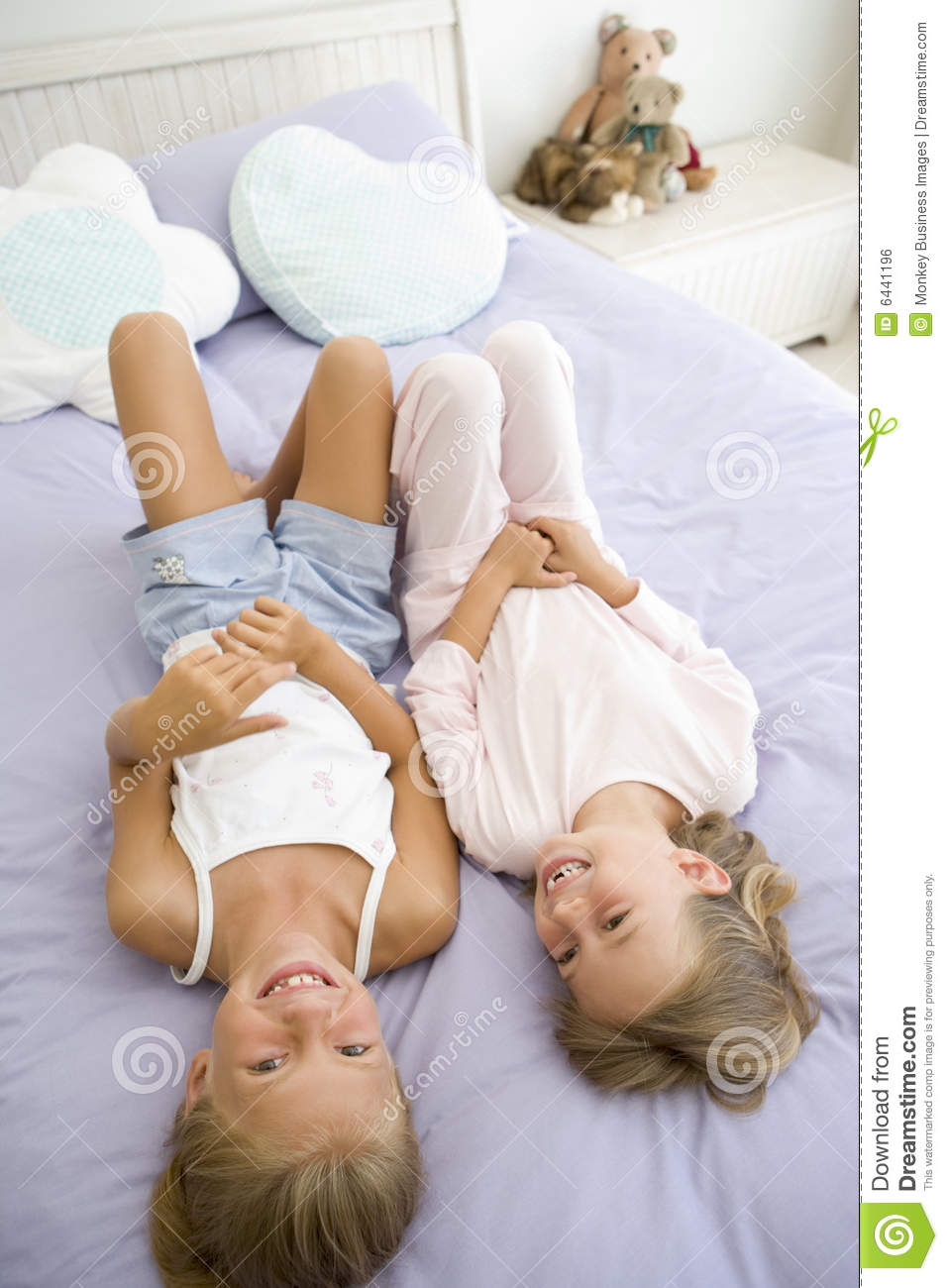 Two Young Girls In Their Pajamas Lying On A Bed Stock