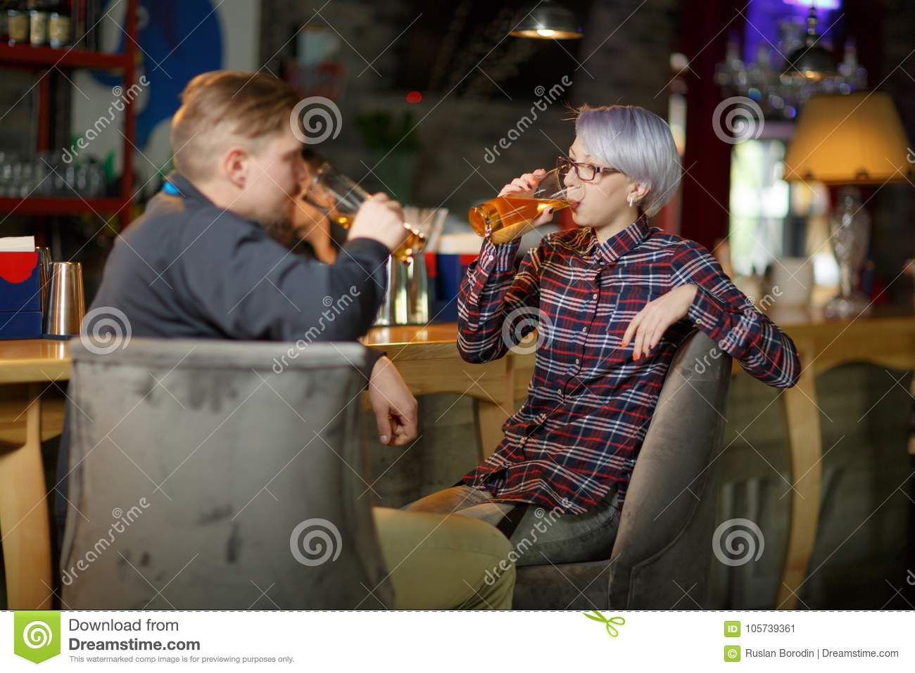 Guys and a girl are drinking beer sitting in a bar. Indoors.