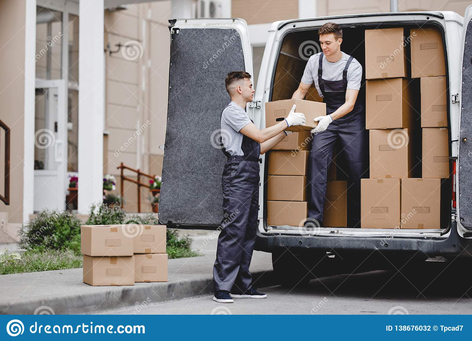 Two young handsome movers wearing uniforms are unloading the van full of boxes. House move, mover service