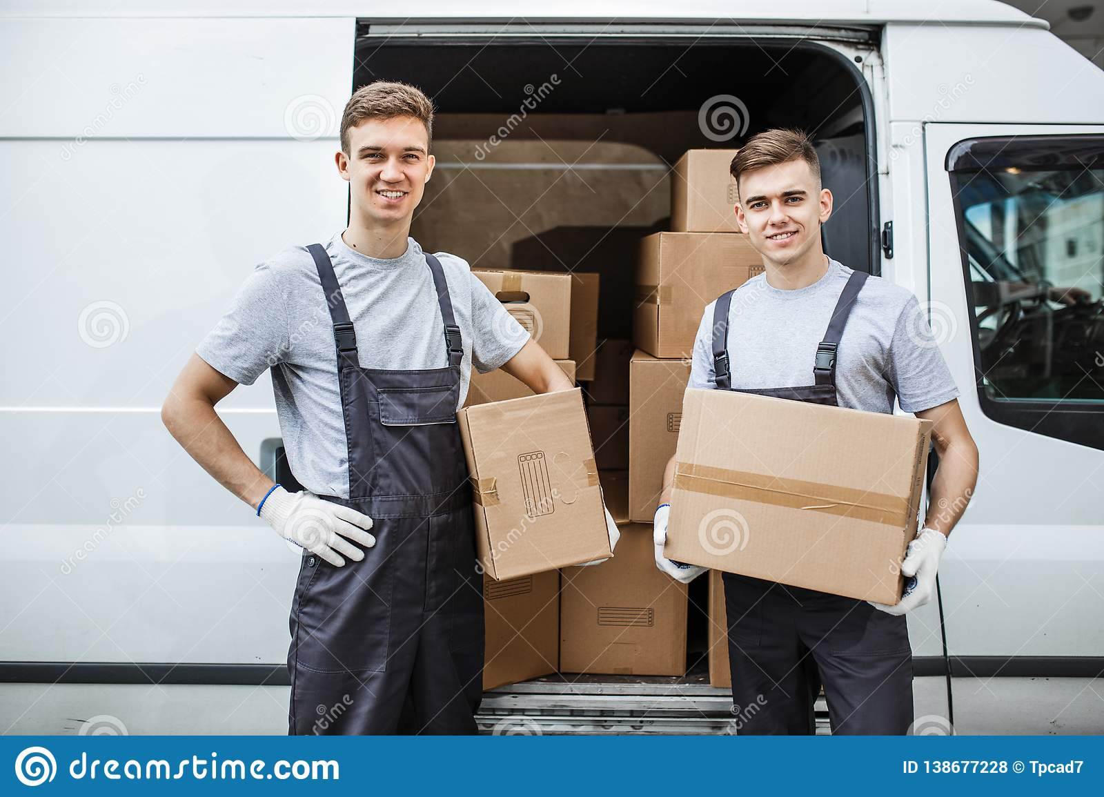 Two young handsome smiling workers wearing uniforms are standing next to the van full of boxes. House move, mover