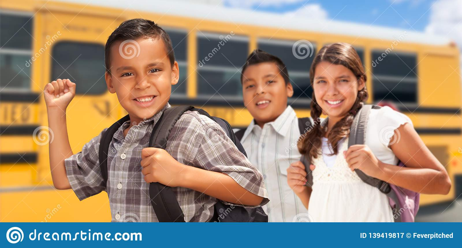Excited Young Hispanic Boys and Girl Walking Near School Bus
