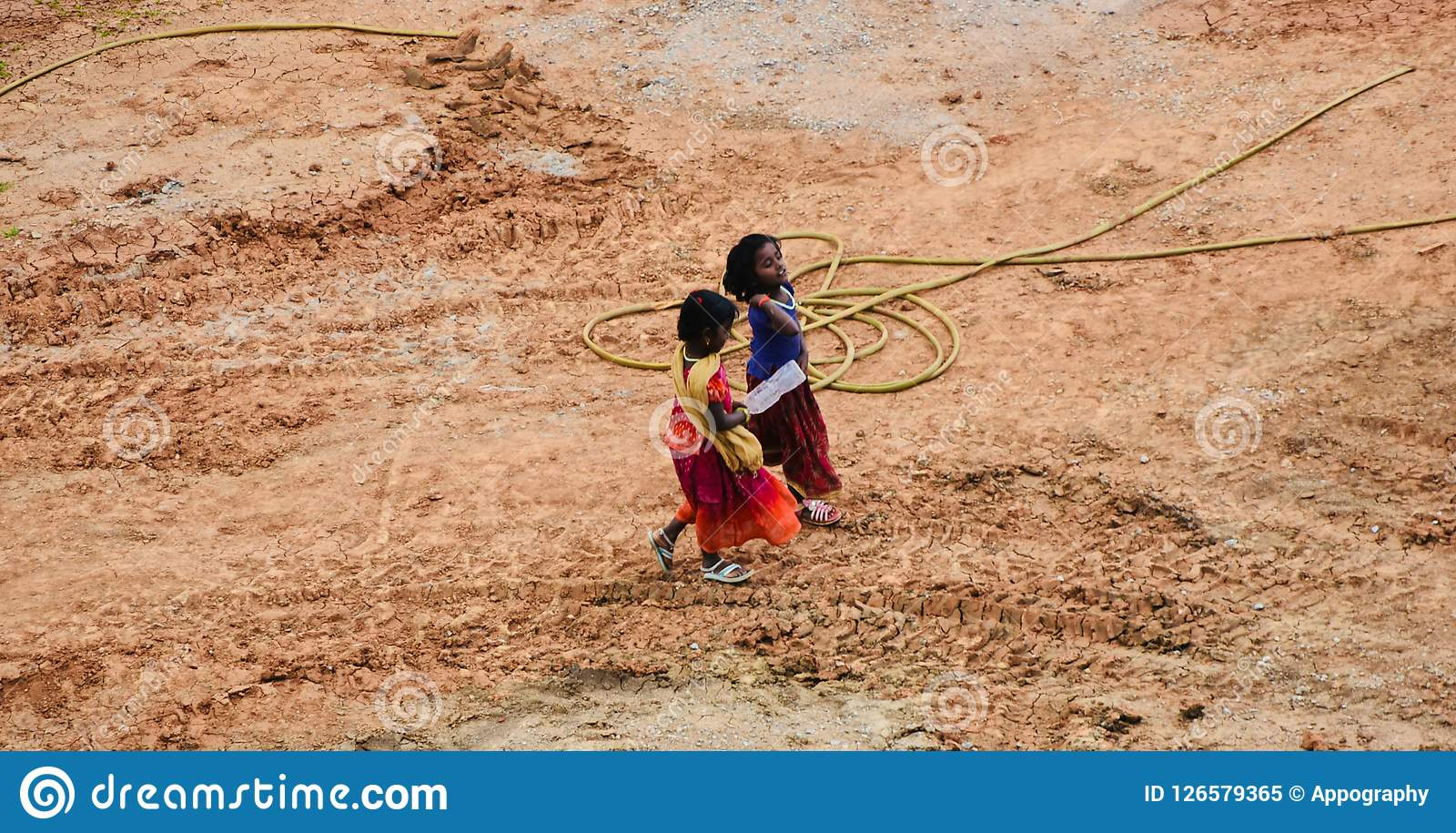 Two young Indian kids walking through a construction site
