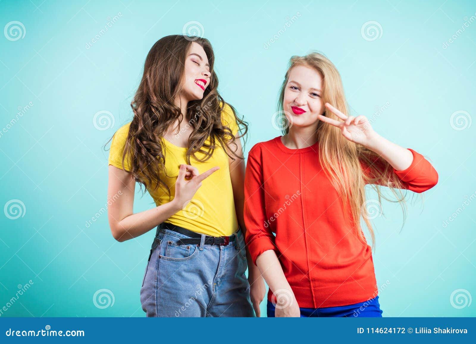 Two young joyful women on blue background. Youth, happiness, fashion, friendshi.