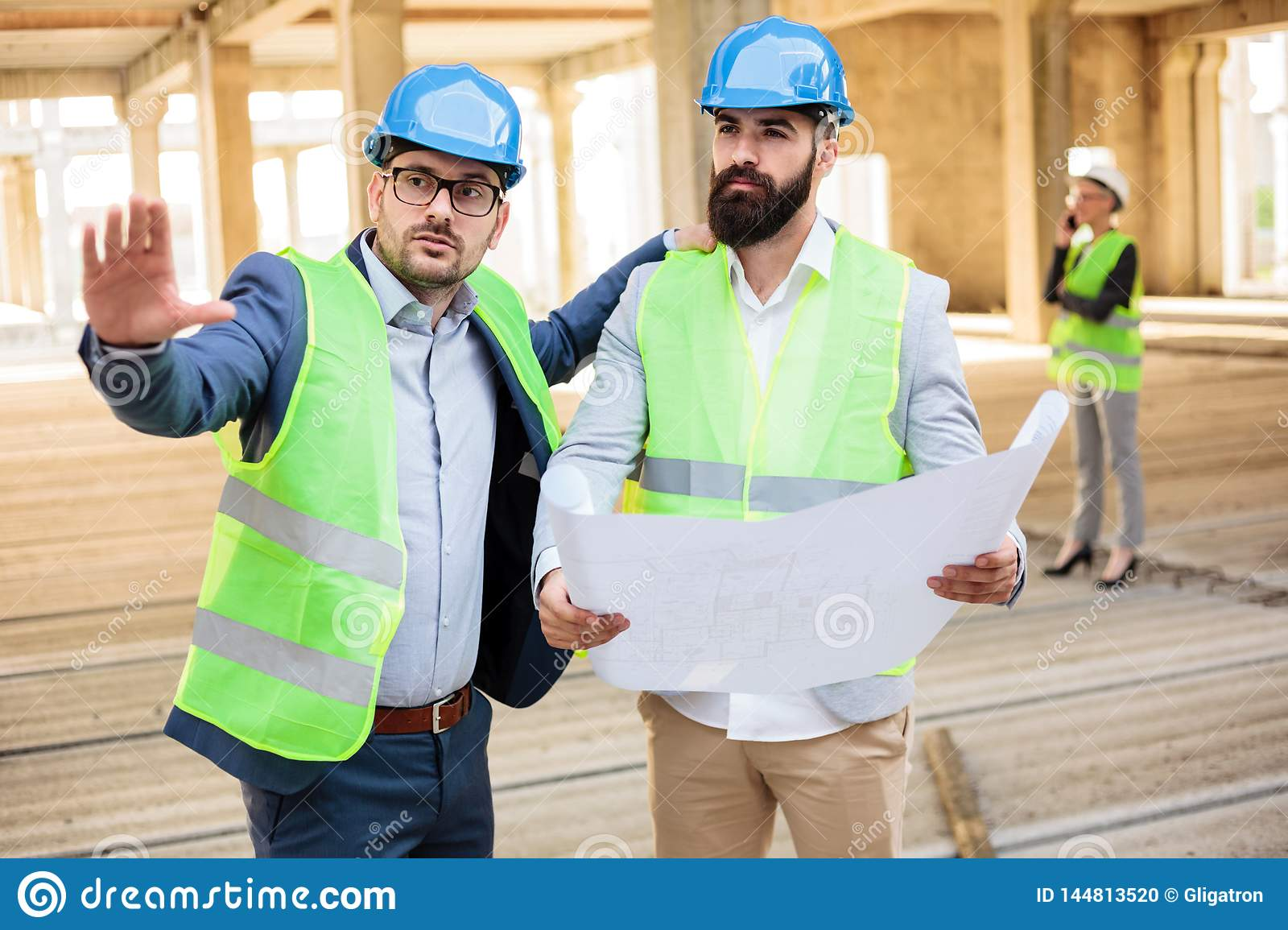 Two young male engineers discussing project details on a construction site