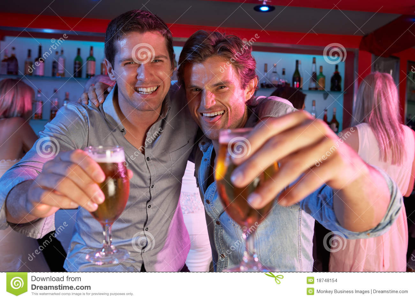 Two Young Men Having Fun In Busy Bar