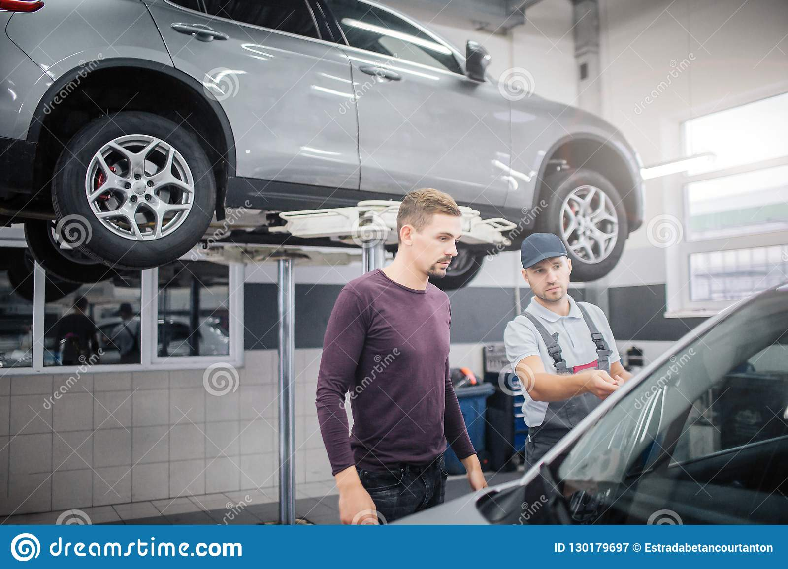 Two young men stand in garage at car. Worker points on automobile. Owner looks at it. They are serious and concentrated