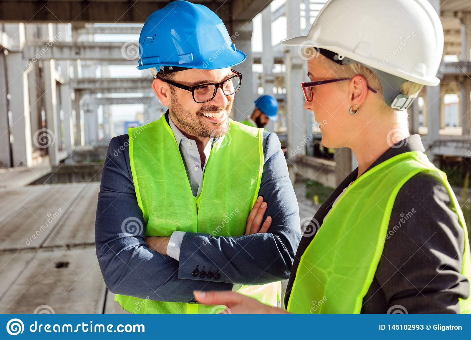 Two young modern architects or civil engineers talking about future project development on a construction site