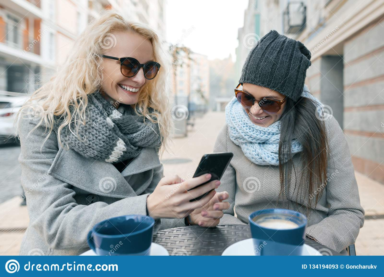 Two young smiling fashionable women having fun in outdoor cafe. Urban background, women laughing looking at mobile phone