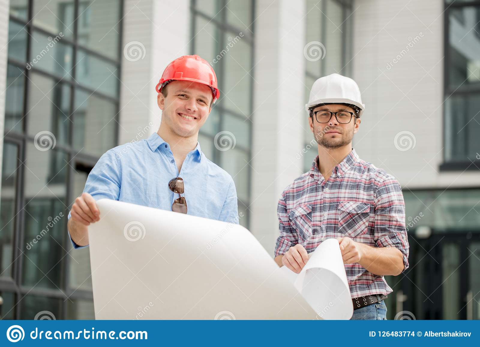 Two young talented engineers are holding scheme of construction