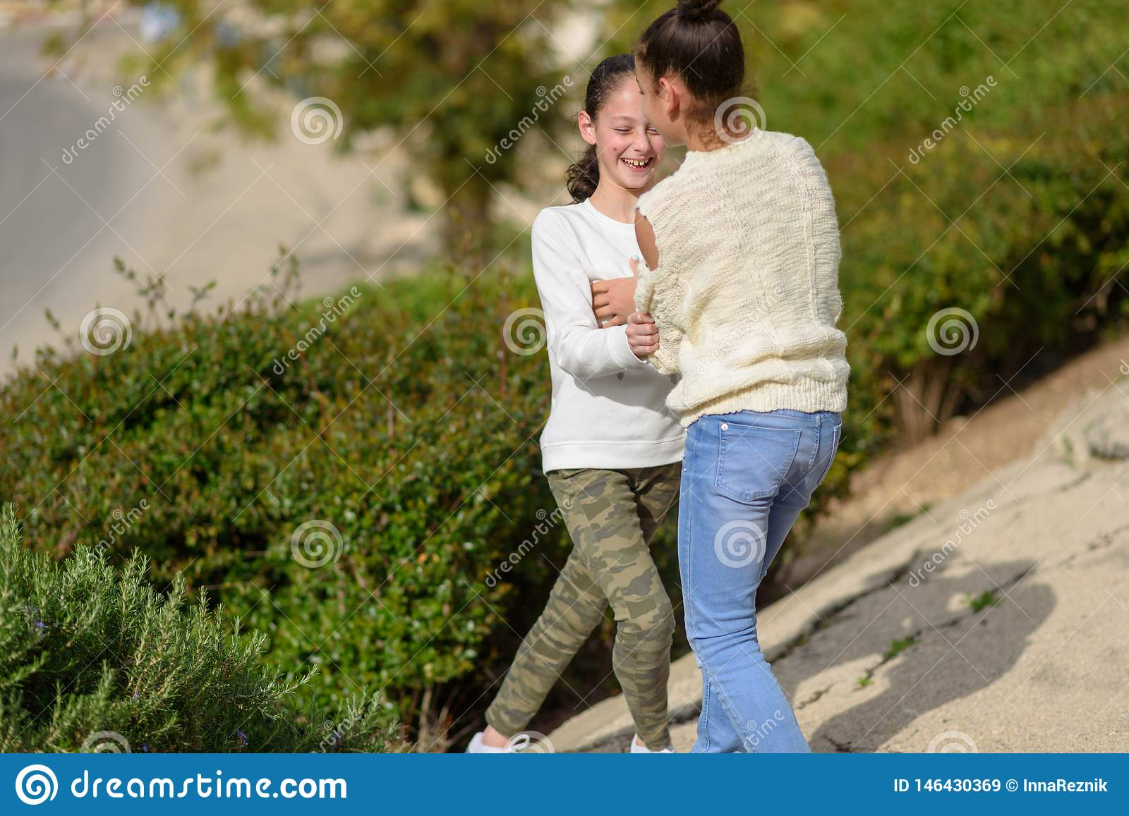 Two Young Teen Girls Playing Outdoor At Sunny Day.