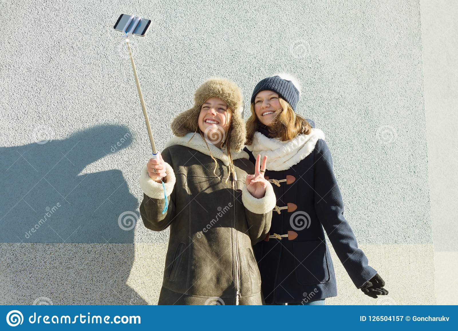 Two young teenage girls having fun outdoors, happy smiling girlfriends in winter clothes taking selfie, positive people and friend
