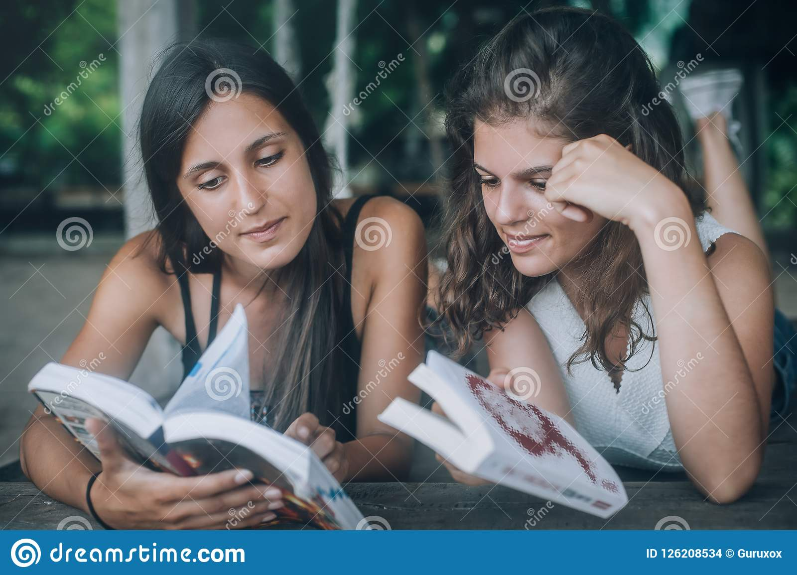 Two young woman lying in swing on beach, reading books