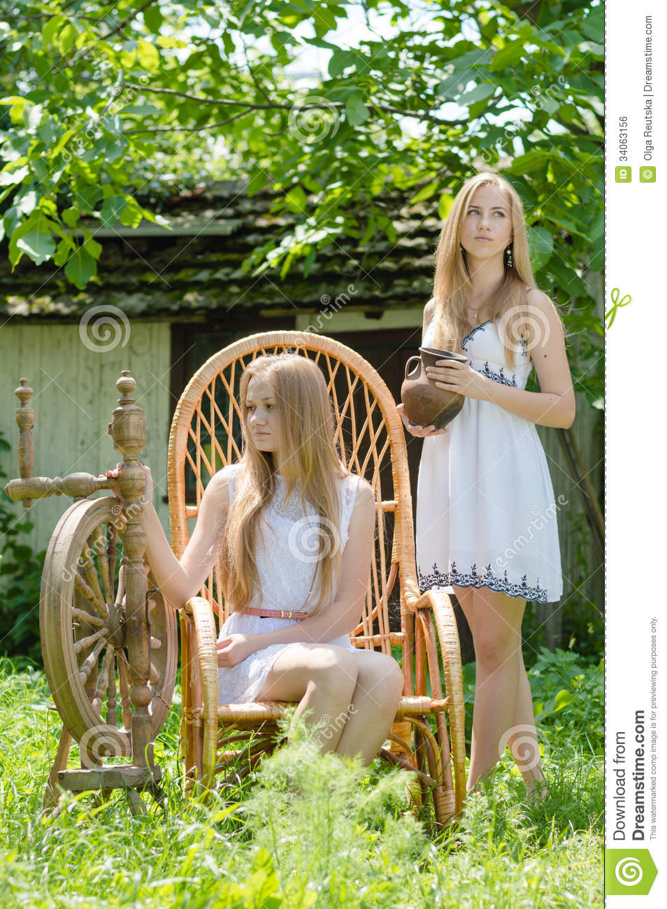 Two Young Women In Country Yard With Spinning Wheel And