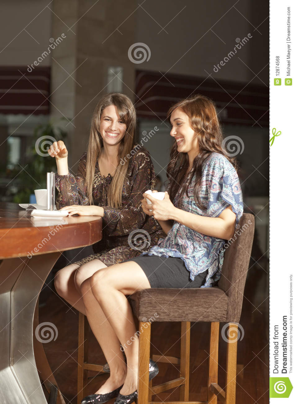 Two Young Women Drinking Coffee At A Bar Royalty Free