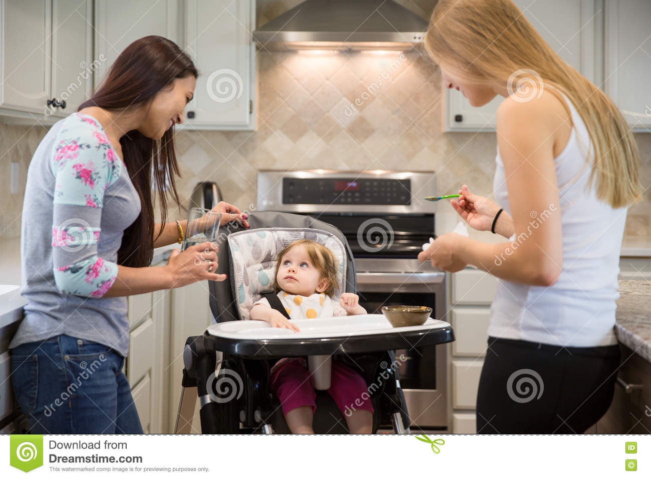 Two Young Women Feeding Little Girl In Highchair. Stock Photo ... b586e13522