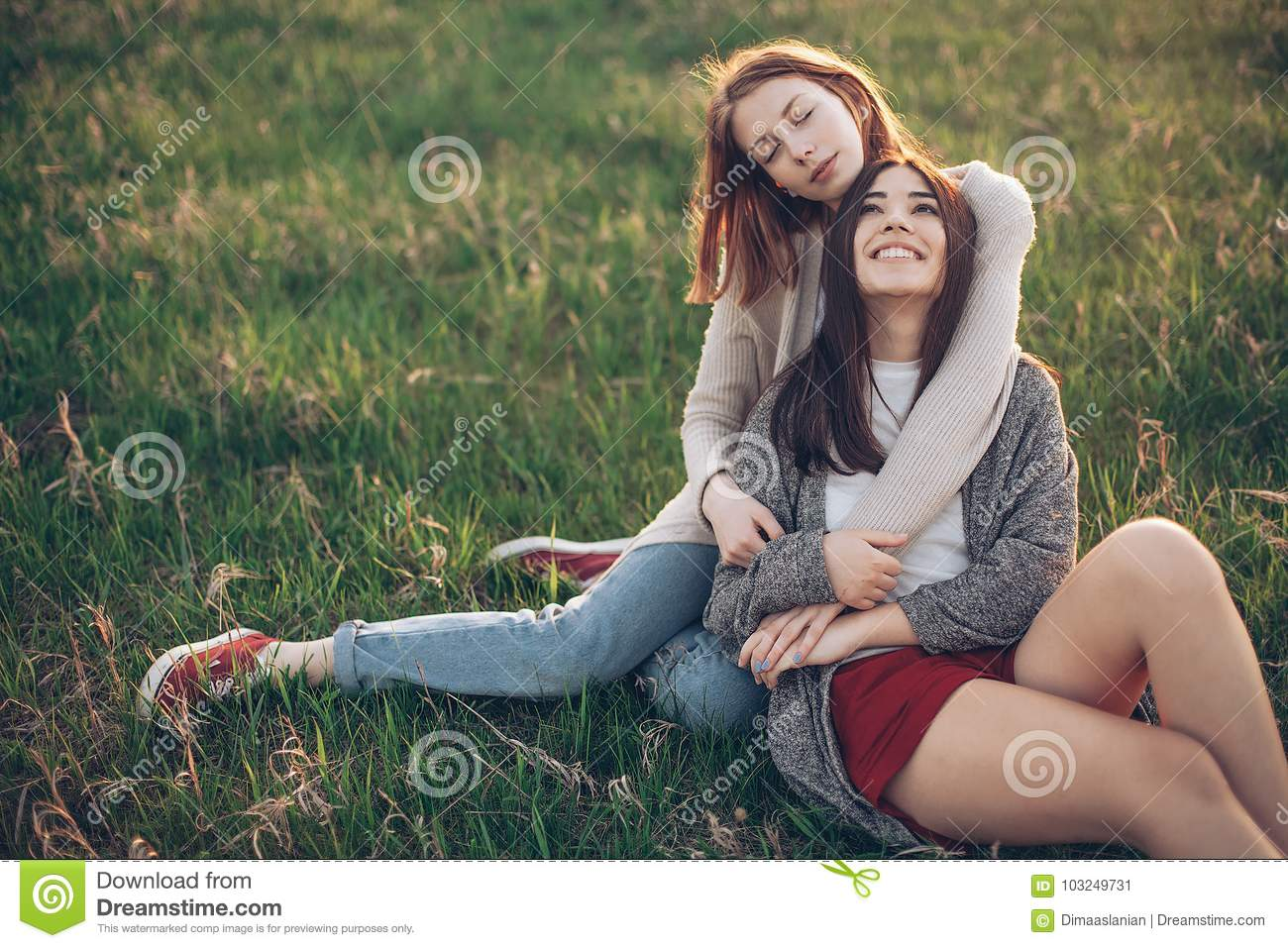 Two young women lying on the grass