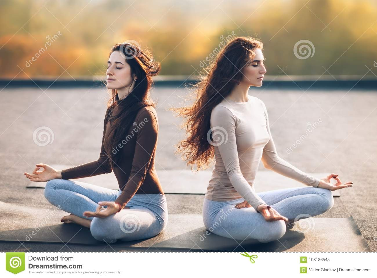 Two young women meditating in Lotus Pose on the roof outdoor