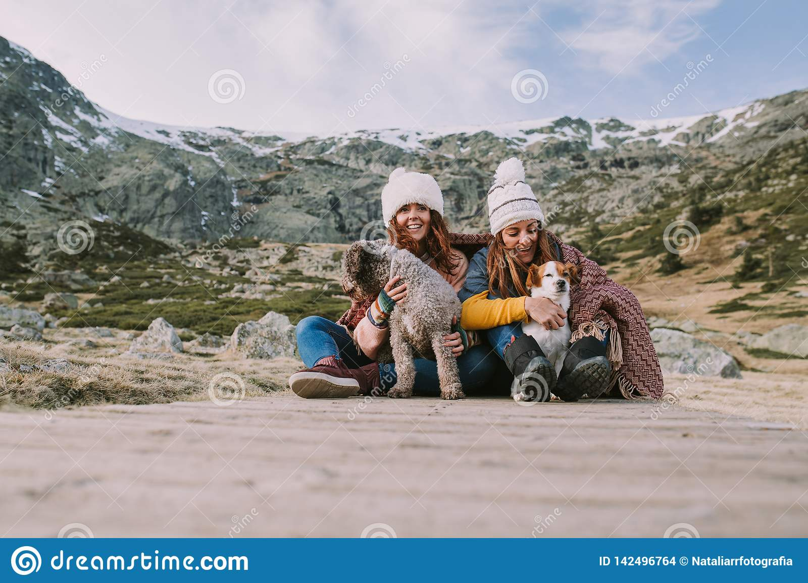 Two young women play with their dogs in the middle of the meadow