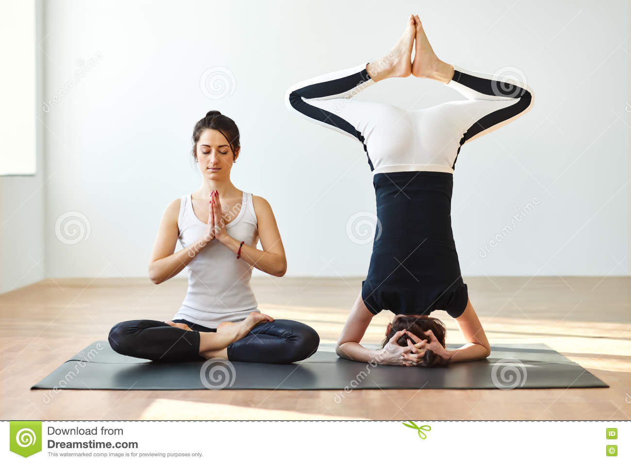 Download Two Young Women Practicing Yoga Poses And Asanas Stock Photo