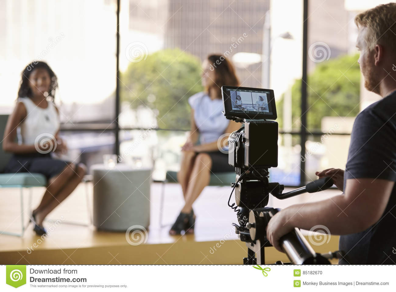 Two young women on set for TV interview, focus on foreground