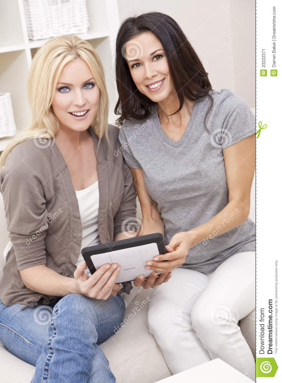 Two Young Women Using Tablet Computer At Home